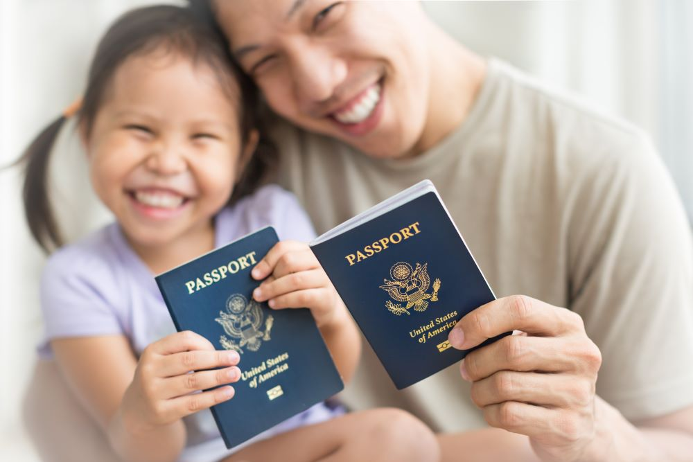 father and daughter smiling and holding USA passports